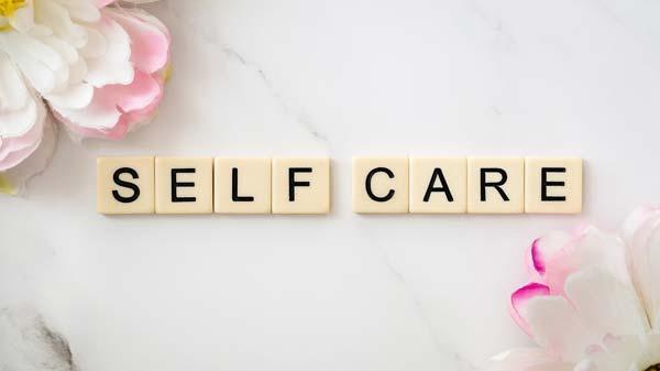 Self care spelled out with scrabble tiles